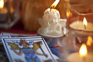 Angel tarot card desk next to multiple candles including a cherub angel candle.