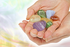 Two cupped hands holding a variety of colorful gemstones.