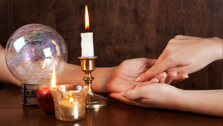 A photo of 2 people's hands together while one person gives the other a palm reading.  A candle and crystal ball sit nearby.